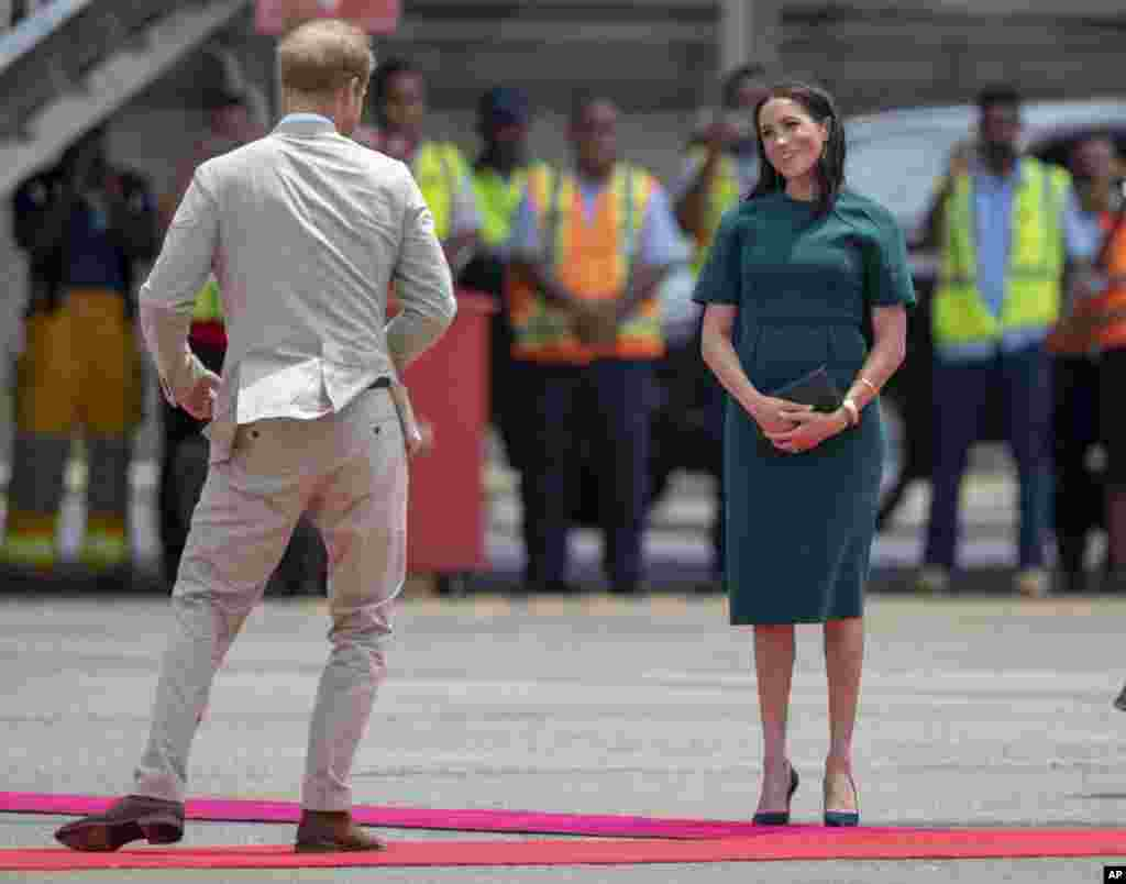 Britain's Prince Harry and Meghan, Duchess of Sussex, react before boarding their flight in Nadi, Fiji.