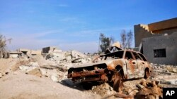 FILE - A burned out car lies amid damaged buildings in Ramadi, 70 miles (115 kilometers) west of Baghdad, Iraq, on Jan. 2, 2016.