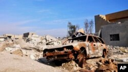 A burned out car lies amid damaged buildings in Ramadi, 70 miles (115 kilometers) west of Baghdad, Iraq, on Jan. 2, 2016. Iraq's military says Islamic State militants launched attacks Friday with seven suicide car bombs.