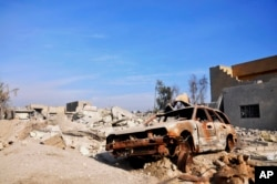 FILE - A burned out car lies amid damaged buildings in Ramadi, 70 miles (115 kilometers) west of Baghdad, Iraq, Jan. 2, 2016. Islamic militants were blamed for the attack.