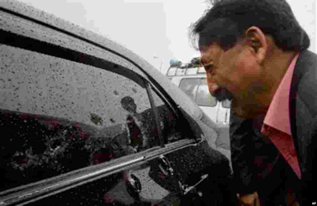 Wasif Ali Khan, a friend of Shahbaz Bhatti looks at the bullet-riddled window of car while he mourns over his death outside a hospital in Islamabad, Pakistan, March 2, 2011.