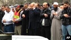 El Dr. Mohammad Yousif Abu-Salha (con las manos en la cabeza) dirige las oraciones durante el funeral de sus dos hijas en Chapel Hill.