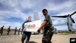 菲律宾和美国军人携手把美国救灾物资卸下美国鱼鹰军机。(2013年11月20日)
