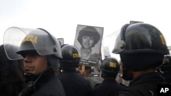 Demonstrators shout slogans against a medical pardon to former President Alberto Fujimori with photographs of people slain during his decade in power, as they confront riot police in Lima, Peru, Monday, Dec. 25, 2017.