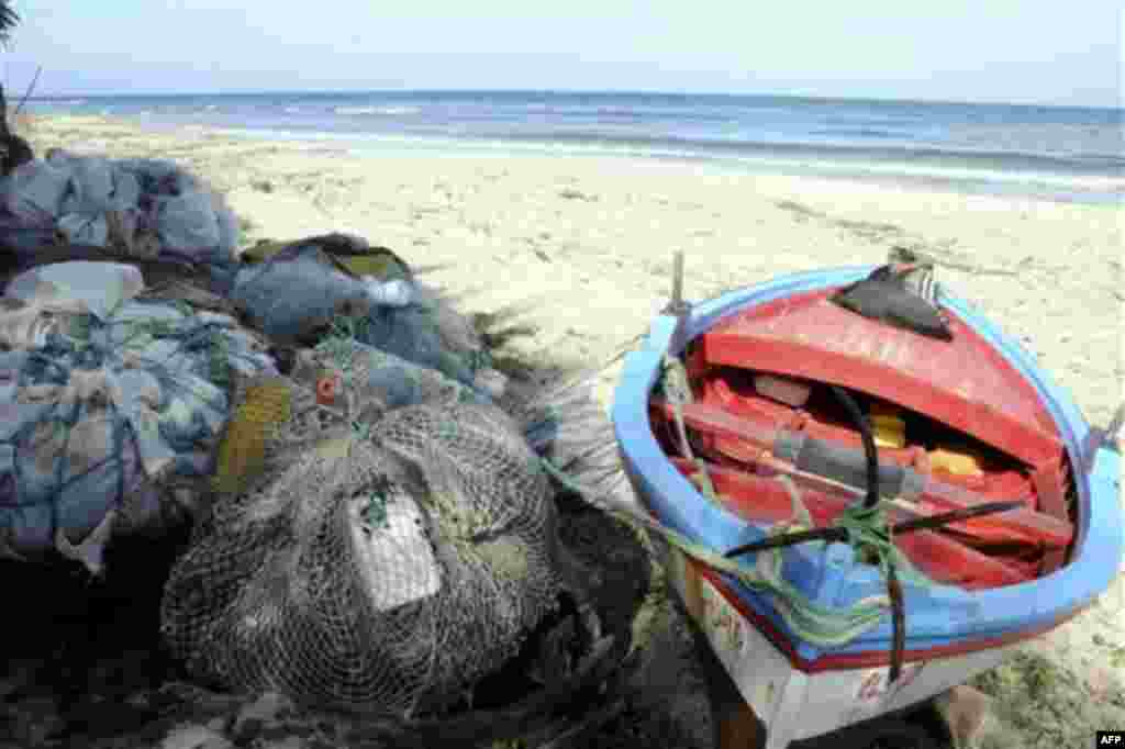 A fisherman's boat is seen on a beach at Sounine, Tunisia, Tuesday Feb. 15, 2011. The village is one of the departing site for would-be immigrants from North Africa toward Italy's shores, despite hours of sailing. More than 4,000 migrants have landed on t