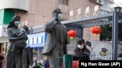 资料照片:在中国武汉市,一名女子正走过带着口罩的雕塑面前。世卫组织新冠溯源专家小组当时正在武汉考察。(2021年1月29日)