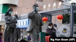 A woman wearing a mask walks past statues with masks placed on them in Wuhan in central China's Hubei province on Friday, Jan. 29, 2021. A World Health Organization team is visiting the central city of Wuhan where the coronavirus was first detected. (AP Photo/Ng Han Guan)