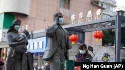 资料照片:中国武汉市,一名女子正走过带着口罩的雕塑面前。期间,世卫组织新冠溯源专家小组正在武汉考察。(2021年1月29日)