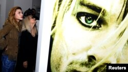 "Kurt Cobain's daughter Frances Bean Cobain, left, attends the opening of the ""Growing Up Kurt Cobain"" exhibition, featuring personal items of Nirvana frontman Kurt Cobain, at the museum of Style Icons in Newbridge, Ireland, July 17, 2018."