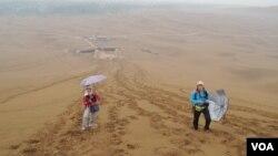 在鄯善庫木塔格沙漠遇上難得的沙漠雨,沙漠被雨水潤濕後,留下很多 較結實的腳印,遠處的鄯善城區亦籠罩在雨霧中