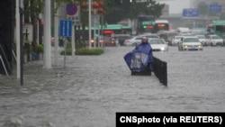 中國河南省鄭州市一名市民站在洪水氾濫的街道上。(2021年7月20日)