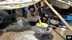 یک زن آواره در حال هم زدن خوراکی که از غلات ارسالی برنامه جهانی غذا درست شده - جوبا، دسامبر ۲۰۱۳