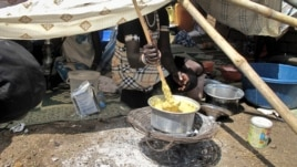 A displaced woman stirs fortified cereal mix at the U.N. compound where she has sought shelter in Juba, Dec. 23, 2013.
