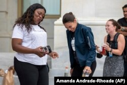 """Rep. Cori Bush, D-Mo., and Rep. Alexandria Ocasio-Cortez, D-N.Y., have an impromptu dance party to """"Run the World (Girls)"""" by Beyonce after it was announced that the Biden administration will enact a targeted nationwide eviction moratorium outside of Capitol."""