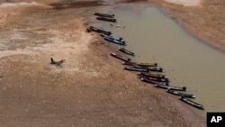 FILE - Fishing boats park downstream from Lamtakong dam during a recent period of extreme drought in Nakhon Ratchasima, Thailand.