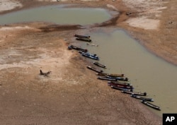 FILE - Fishing boats park downstream from Lamtakong dam during a recent period of extreme drought in Nakhon Ratchasima, Thailand, June, 29, 2015.
