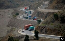 Trucks carry goods to neighboring Afghanistan through the Khyber Pass in Pakistani tribal area, March 21, 2017. A Pakistani border official says hundreds of trucks have crossed into Afghanistan after the border reopened for the first time in a month.