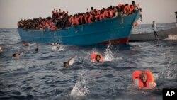 29일 리비아 북부 해상에서 목조 선박에 탄 난민들이 구조를 받기 위해 바다로 뛰어들고 있다. 난민들은 대부분 에리트레아 출신이었다.