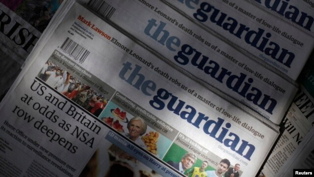 FILE - Copies of the Guardian newspaper are displayed at a news agent in London, Aug. 21 2013.