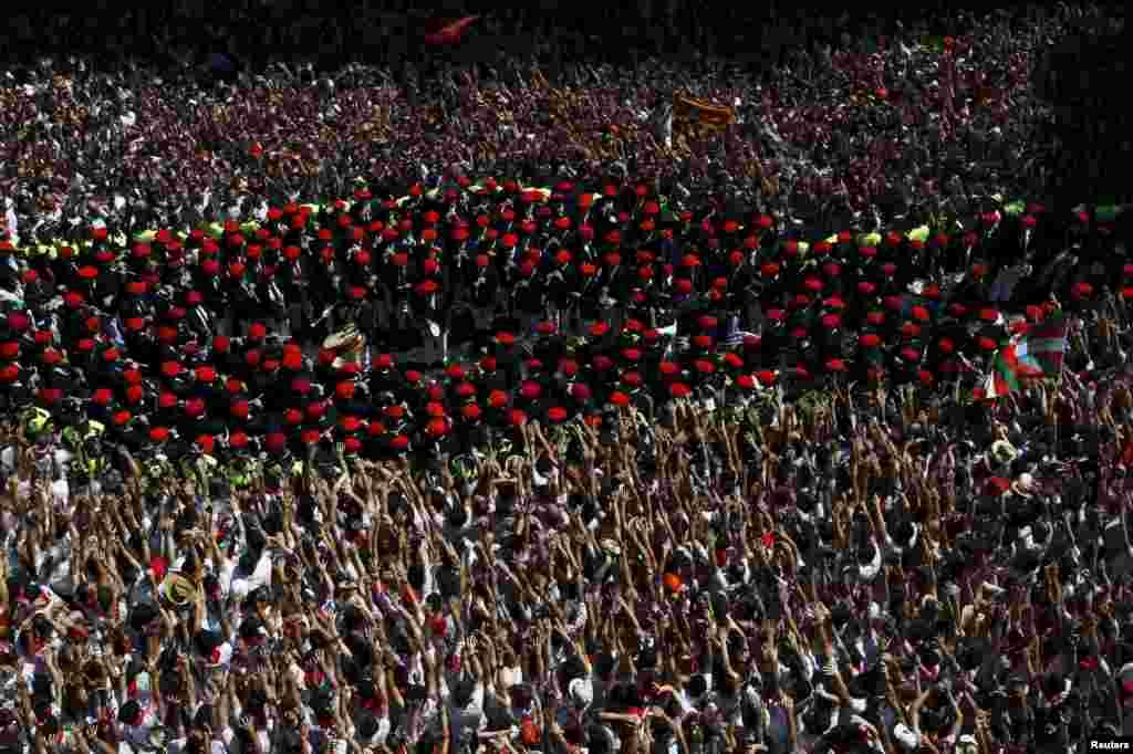 """A banda municipal da Pamplona passa por participantes no Festival de São Firmino na praça da câmara municipal em Pamplona, Espanha. O festival, bem conhecido pela sua """"corrida de touros,"""" começou com a tradição do lançamento do foguete, chamado """"chupinazo"""". 6 de Julho, 2015."""