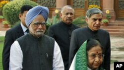 India's Prime Minister Manmohan Singh (in blue turban) and President Pratibha Patil arrive at the parliament on the first day of the budget session in New Delhi. The government will battle both inflation and corruption, February 21, 2011