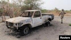 A Nigerian soldier walks past a burnt vehicle during a military patrol in Hausari village, near Maiduguri, June 5, 2013.