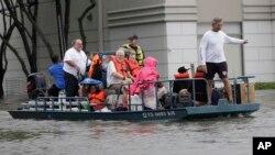 Sekelompok warga sedang dievakuasi dari rumah-rumah mereka yang dikepung banjir akibat Badai Tropis Harvey, Minggu 27 Agustus 2017, di Houston, Texas.