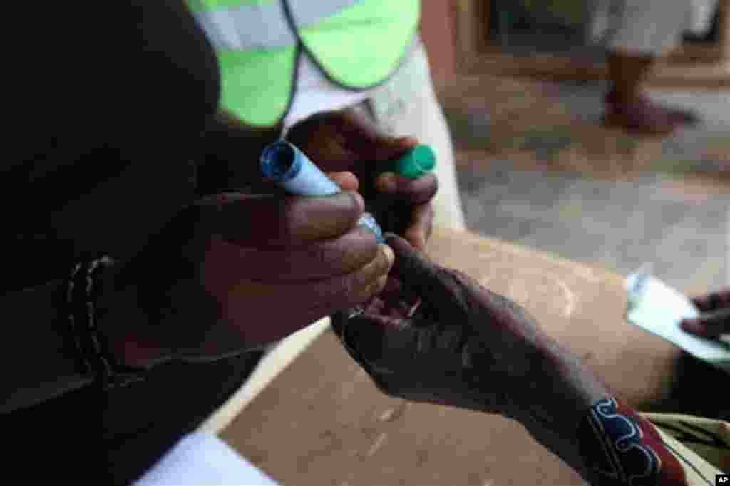 An unidentified person is marked with indelible ink after he was registered at a polling station at Oyeleye in Ibadan, Nigeria, Saturday, April 9, 2011.