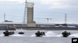 Police and Royal Marines boats perform during a combined Police and Royal Marines security exercise on the River Thames in London in preparation for the 2012 Olympics, January 19, 2012.