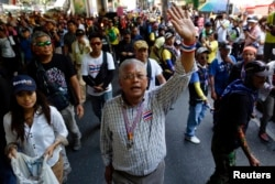 Anti-government protest leader Suthep Thaugsuban waves to his supporters as he leads a march in central Bangkok May 8, 2014.