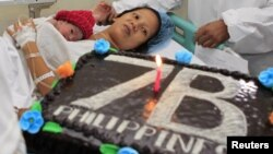 United Nations Population Fund staff gives a cake to the family of newborn baby girl named Danica Camacho, the Philippines' symbolic 'seven billionth baby' who is part of the UN's seven billion global population projection, in Fabella Maternity hospital i