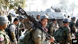 Cambodian soldiers carry their weapons near Preah Vihear temple along the border with Thailand, February 6, 2011