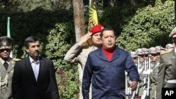 Venezuelan President Hugo Chavez, center left, reviews an honor guard, as he is accompanied by his Iranian counterpart Mahmoud Ahmadinejad, left, during an official welcoming ceremony, in Tehran, Iran, 19 Oct. 2010