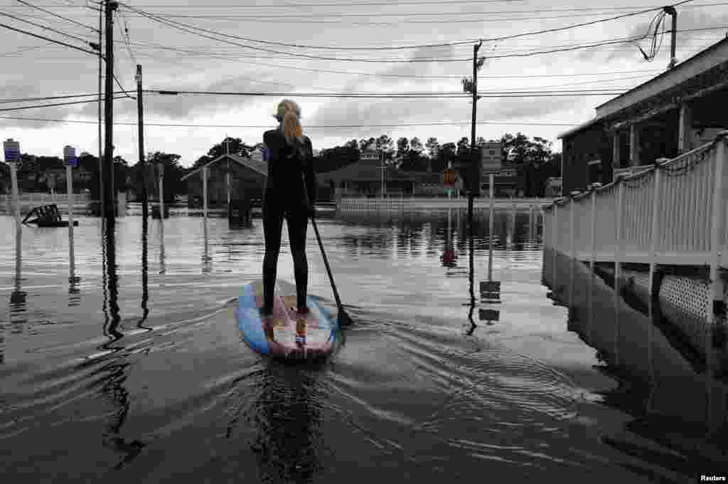 Zoe Jurusik  paddleboards down a flooded city street after Hurricane Sandy in Bethany Beach, Delaware, Oct. 30, 2012.