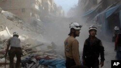 In this picture provided by the Syrian Civil Defense group known as the White Helmets, Syrian Civil Defense workers search through the rubble in rebel-held eastern Aleppo, Syria, Oct. 12, 2016. The situation in Aleppo is among the focal points of the Lausanne talks.