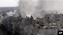Image made from amateur video released by Shaam News Network and accessed June 8, 2012, purports to show explosions in the Khaldiyeh area of Homs, Syria.
