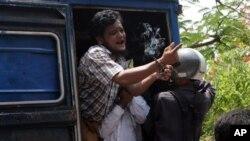 Salah seorang dari tujuh pria yang ditangkap atas tuduhan pembunuhan seorang biksu, berteriak dari kendaraan yang membawanya ke pengadilan di Meikhtila, Burma (21/5).