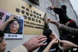 FILE - Protesters post photos of missing booksellers during a protest outside the Liaison of the Central People's Government in Hong Kong, Jan. 3, 2016.