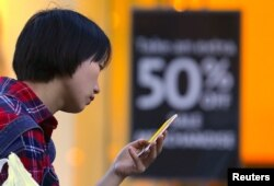 FILE - A shopper looks at her phone in front of a sales sign displayed in a window of a retail store at a shopping center in central Sydney, Australia.