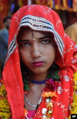 FILE - Child bride Laxmi, 14, looks on at the Balaji temple in Kamkheda village, in the western Indian state of Rajasthan, May 7, 2011.