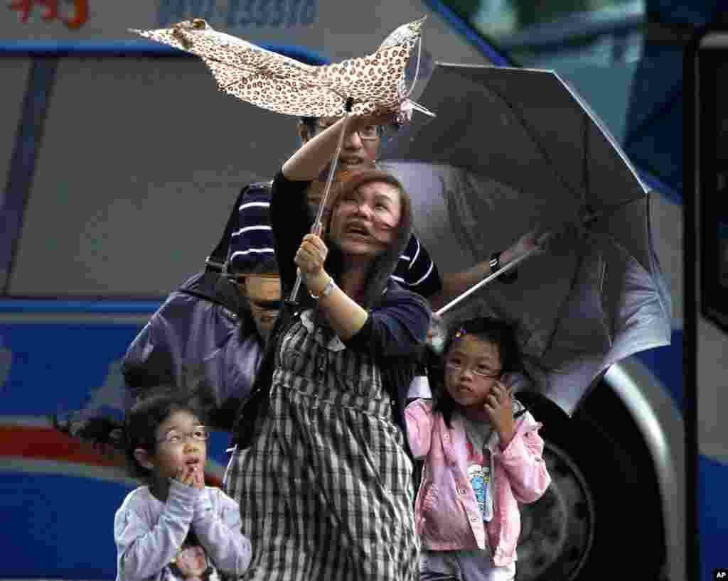 Bà mẹ chống đỡ với gió lớn của bão Saola ở Đài Bắc, Đài Loan, 1/8/2012.