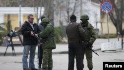 軍警在克里米亞首府辛菲羅波爾的議會附近檢查記者的證件