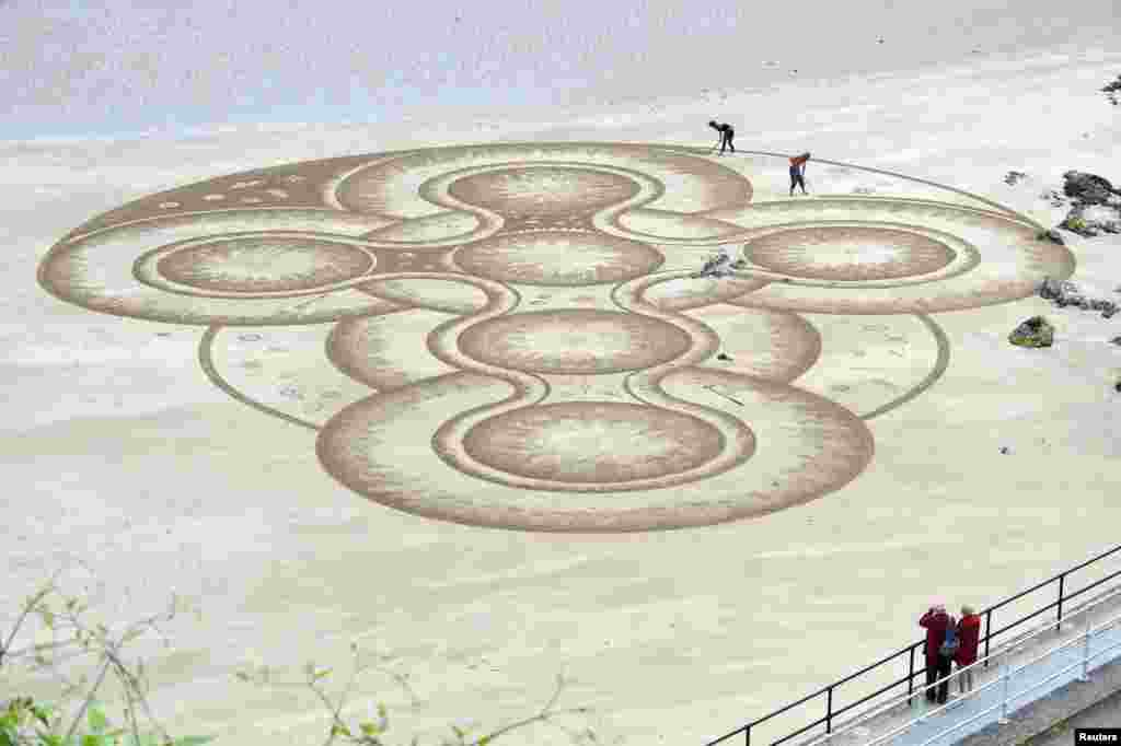 Sand artist Marc Treanor creates a work on the North Beach at Tenby Harbour, Pembrokeshire, Wales, Britain.