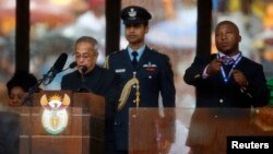India's President Pranab Mukherjee speaks at the podium as the fake sign language interpreter (R) punches the air beside him during a memorial service for late South African President Nelson Mandela at the FNB soccer stadium in Johannesburg, Dec. 10, 201