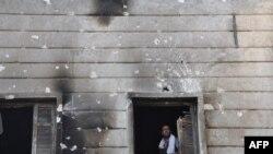 Borac Sirijske slobodne armije na prozoru izgorele policijske stanice u Alepu