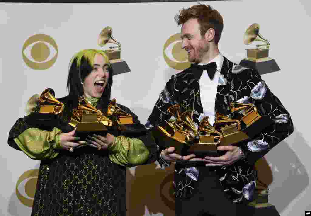 "Billie Eilish, left, and Finneas O'Connell pose in the press room with the awards for best album, best engineered album and best pop vocal album for ""We All Fall Asleep, Where Do We Go?,"" best song and record for ""Bad Guy,"" best new artist and best producer, non-classical at the 62nd annual Grammy Awards at the Staples Center in Los Angeles, Jan. 26, 2020."