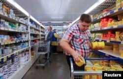 Nhân viên cửa hàng Metro Cash and Carry ở Moscow xếp pho mát lên kệ.