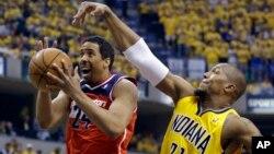 Davis West, de los Pacers, intenta bloquear al escolta Andre Miller de los Wizards, en el primer juego de la serie que ganaron estos últimos, en Indiana.