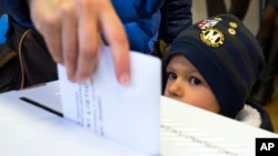 FILE - A child looks at a ballot being cast at a polling station in Zagreb, Croatia, Nov. 8, 2015.