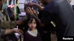 A girl looks on following alleged chemical weapons attack, in what is said to be Douma, Syria in this still image from video obtained by Reuters. (April 8, 2018.)